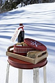 Tray of red wine, biscuits & cheese on a stool in snow