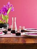 Gedeckter Tisch mit Rotwein und Cattleya-Orchidee