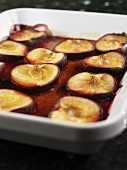 Plum halves in sauce in a baking dish