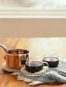 Mulled wine in glass cups and in copper pan