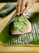 Wrapping fillet of striped bass with herb paste in banana leaf