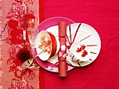 Place-setting with sparkling wine glass on pink background