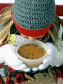 Girl in winter clothes drinking hot soup