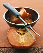 Persimmon in and beside metal bowl with carving fork
