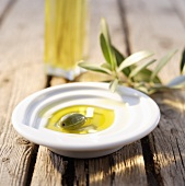 Small dish of olive oil with green olive