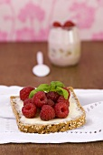 Fresh raspberries and basil on a slice of bread and butter