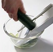 Slicing a cucumber on a mandolin slicer