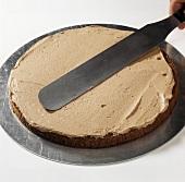 Spreading a sponge base with chocolate cream