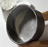 Dusting a greased springform pan with flour