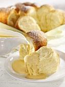 Pouring custard over Buchteln (sweet yeast dumplings)
