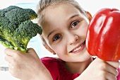 Girl holding broccoli and red pepper