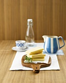 Thick slices of cheese on wooden board, milk jug, cup, bottle