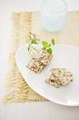 Wholemeal crispbread and herbs on white plate
