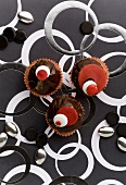Three cupcakes with chocolate icing & coloured chocolate beans