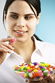 Young woman holding a dish of jelly beans