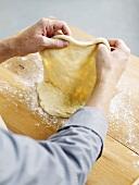 Making pizza dough (pulling the dough)