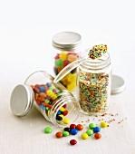 Schokolinsen, Zuckerstreusel und Bonbons in Gläsern