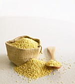 Millet on wooden spoon and in small sack