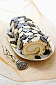 Sponge roll decorated with white and dark chocolate leaves