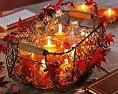 Windlichter im Drahtkorb, dekoriert mit Ahornblättern