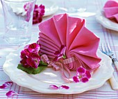 Fächerförmig gefaltete Serviette mit Geranienblüten