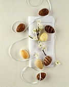 Chocolate Easter eggs and white napkin with flowering twig