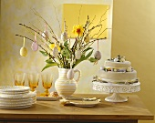 Tiered cake & jug of flowers with biscuits on Easter buffet