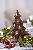 Chocolate Christmas tree among ivy berries
