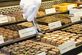 Chocolates with hand and tongs in a confectioner's display