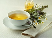 Herb tea with a small bunch of herbs