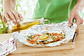 Drizzling fish & vegetables in foil with olive oil