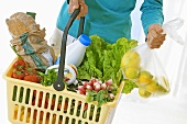 Woman holding a shopping basket full of fresh products