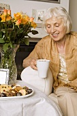 Elderly lady with cappuccino and biscuits