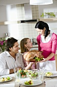 Woman serving roast turkey to the family