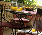 Orange juice and bowl of fruit on table on balcony