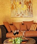 Eingelegte Oliven & Rotwein auf rundem Couchtisch vor Rattansofa mit roten Kissen in Wohnzimmer