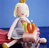 Petit four with birthday candles and crocheted doll