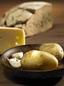 Ingredients for raclette: potato, garlic and cheese