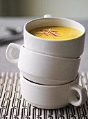 Pumpkin soup with slivers of apple in soup cups