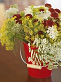 Bunch of flowers (including dill flowers) in a red bucket