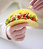 Hand holding taco filled with salad and cheese