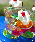 Cubes of coloured jelly with cream and cocktail cherry