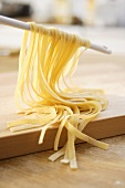 Home-made ribbon pasta hanging over a kitchen spoon