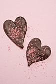 Two chocolate hearts with pink sugar