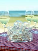 Fairy lights & light bulbs in a bowl & glasses of white wine