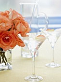 Two glasses of Martini with rose petals, vase of roses