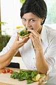 Young woman eating a slice of bread topped with herbs