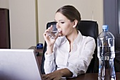 Young woman sitting at computer, drinking water