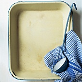 Baking dish with ladle and tea towel