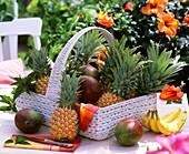 Korb mit Ananas und Mangos, im Hintergrund blühender Hibiskus